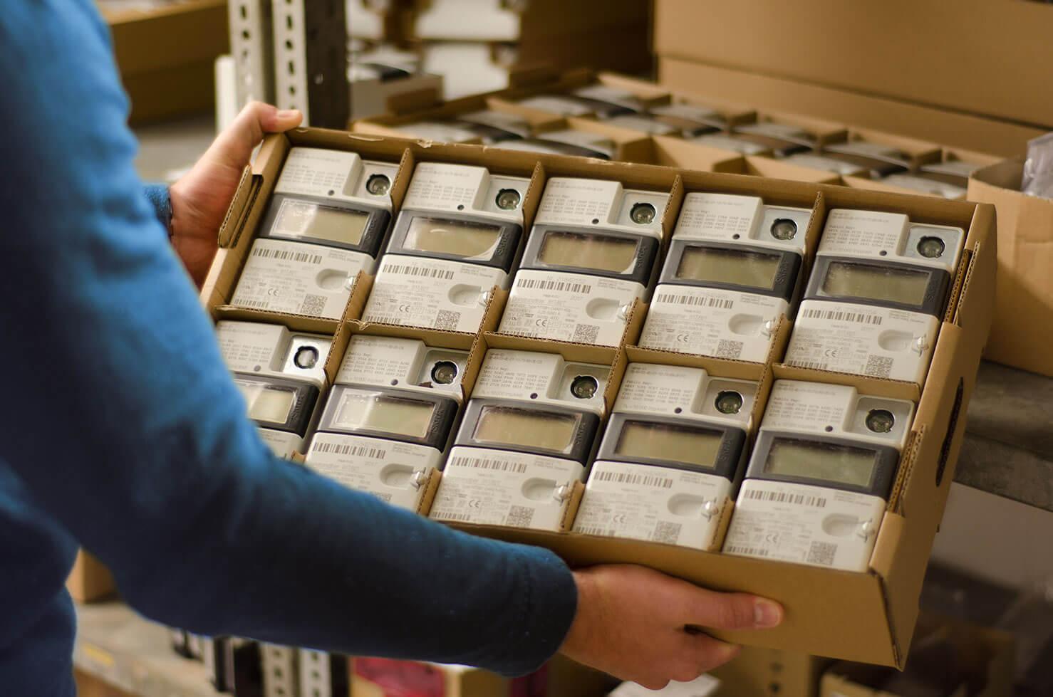 Mitarbeiter der Stadtwerke hebt einen Karton mit digitalen Stromzählern in der Hand.