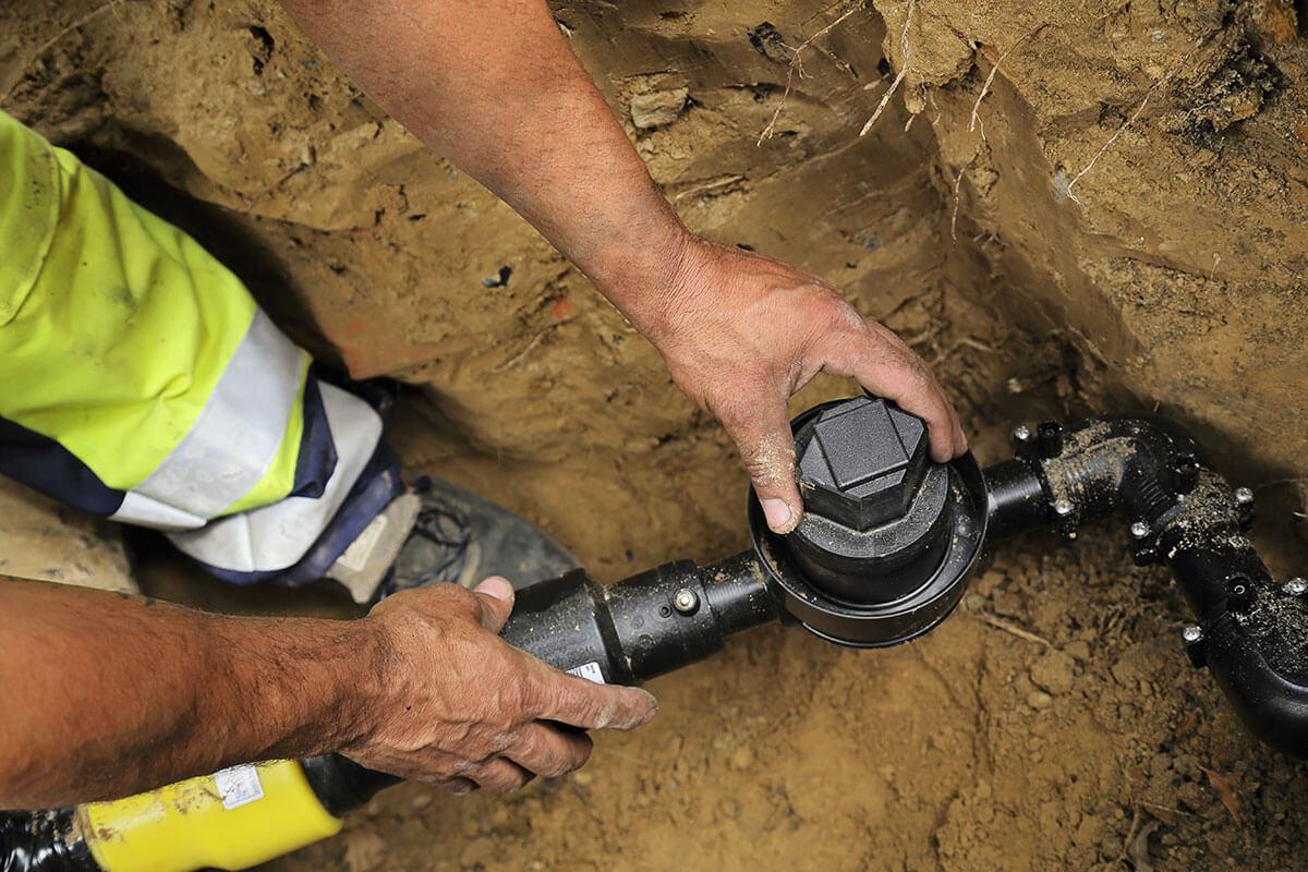 Bauarbeiter prüft mit seinen Händen eine Gasleitung.