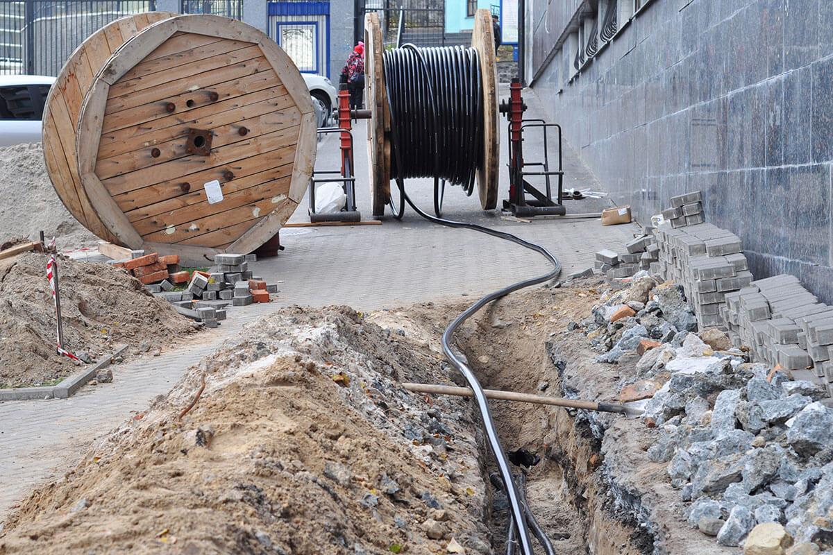 Eine große Kabeltrommel steht an einer Baustelle. Die Kabel verlaufen in das Erdreich.