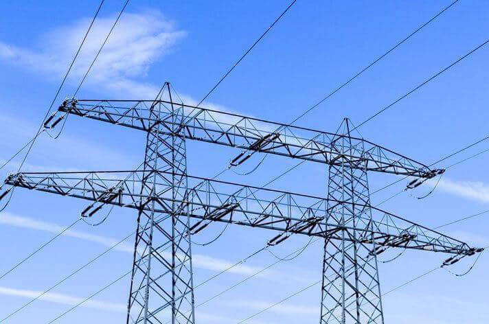 Zwei Strommasten vor blauem Himmel