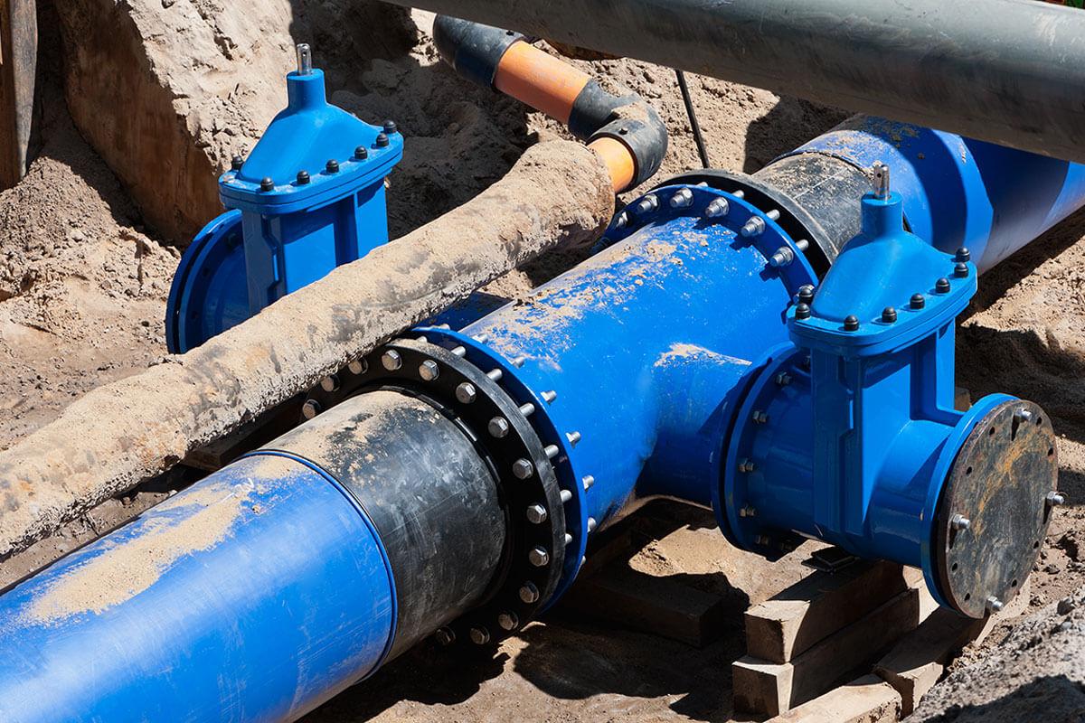Eine blaue Wasserleitung in einem Baugraben.