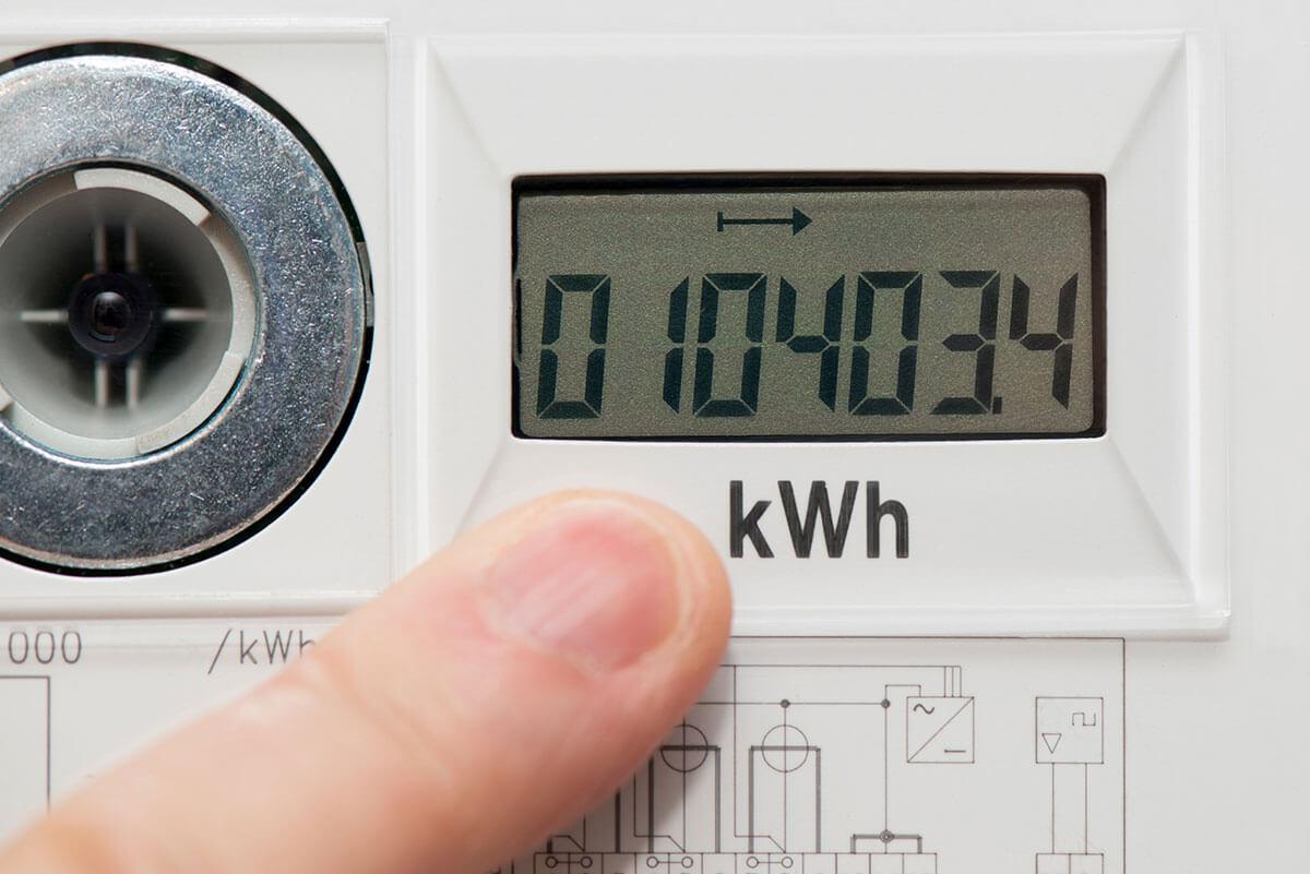 Zeigefinger zeigt auf den Stromverbrauch auf dem Display eines digitalen Stromzählers.